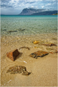 An einem Strand bei Porto Istana an der Costa Smeralda im Nordosten der Insel. Im Hintergrund die Isola Tavolara