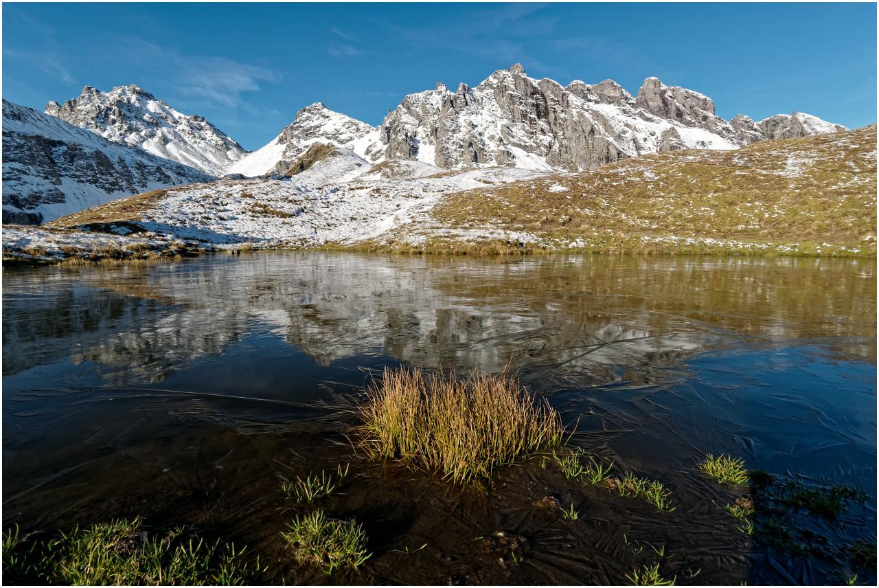 Ein namenloser, vereister Bergsee bei der Bergstation Pizolhütte, im Hintergrund die Schwarzen Hörner