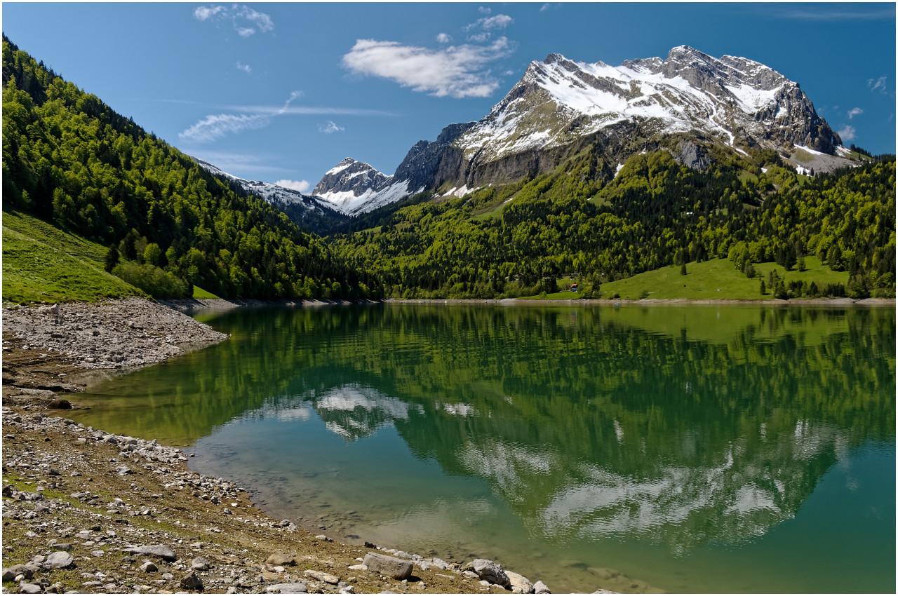 Fluebrig und Gantspitz spiegeln sich im Wägitalersee, der wie im Frühling üblich noch einen sehr tiefen Wasserpegel hat