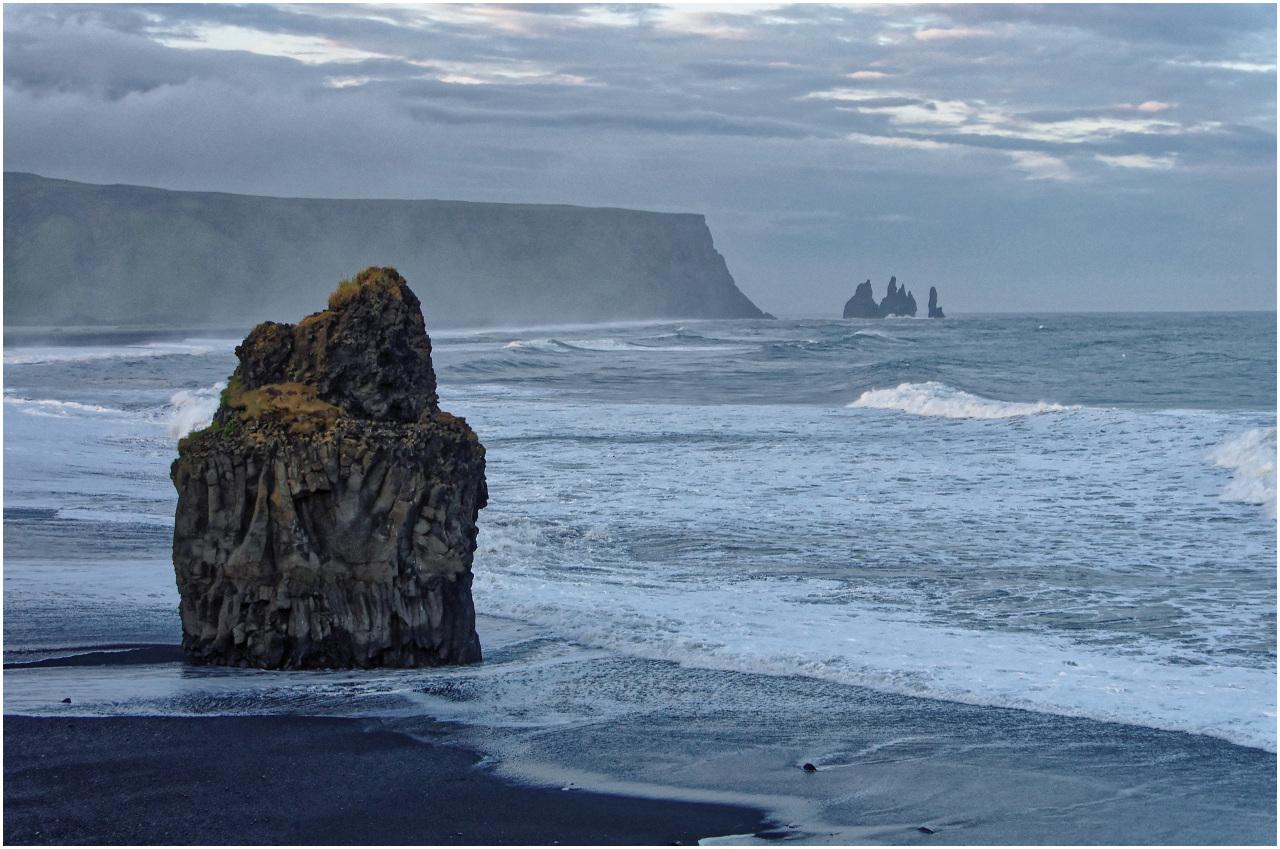 Der Strand Reynisfjara mit dem markanten Felsen und Blick zu den Felsnadeln vor Vík