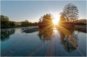 Die Sonne über einer Brücke an der Aaregabelung