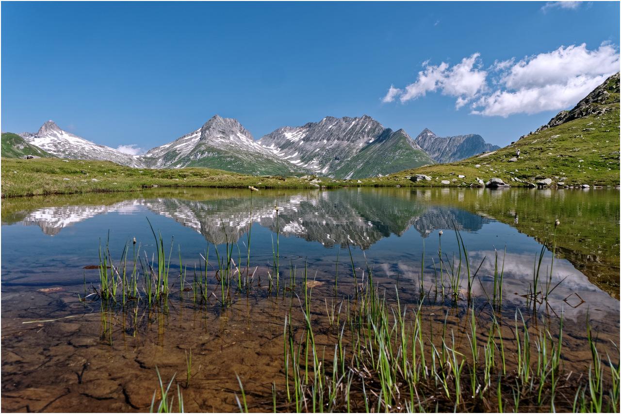 Die Gipfel Piz Tiarms, Piz Giuv, Piz Nair und Chrüzlistock spiegeln sich in einem Moorsee