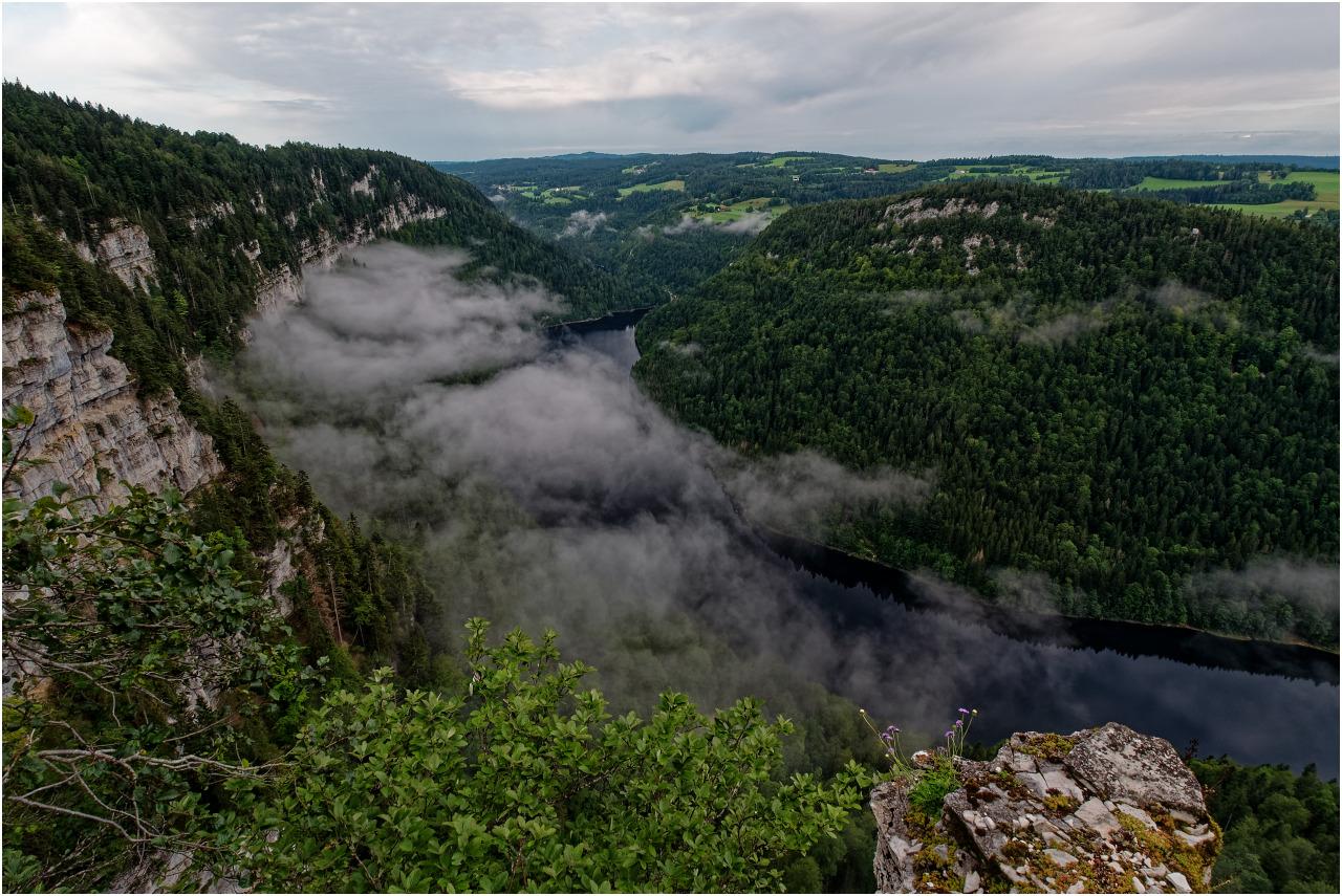 Der erste Blick vom Rocher de Moron über den noch wolkenverhangenen See